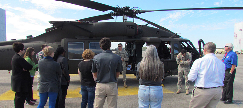 Military men standing in front of helicopter speaking with civilians