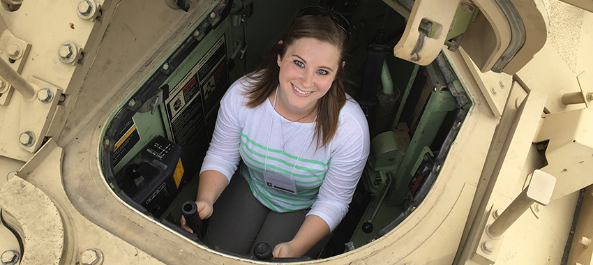 female student sitting in the control center of a tank